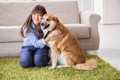 Ο ευτυχής ιδιοκτήτης σκυλιών γυναικών στο σπίτι με χρυσό retriever στοκ εικόνα με δικαίωμα ελεύθερης χρήσης