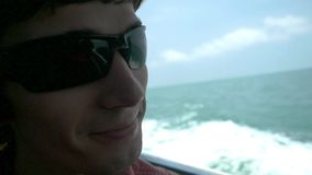 Ο ευτυχής μοντέρνος νεαρός άνδρας μέσα στη μουσική κοντά στη θάλασσα θαλασσίως επιπλέοντας κίνηση αργή 1920x1080 απόθεμα βίντεο