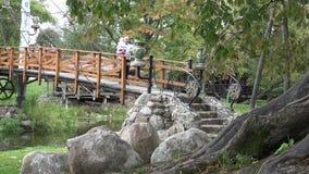 Ο ευτυχής μπαμπάς πατέρων με την κόρη μωρών θαυμάζει τη φύση στη γέφυρα μέσω του ποταμού 4K απόθεμα βίντεο