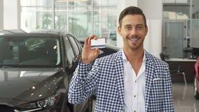 Ο ευτυχής νέος αγοραστής αυτοκινήτων παρουσιάζει πιστωτική κάρτα του στοκ εικόνες