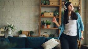 Ο ευτυχής νέος γυναικείος απρόσεκτος σπουδαστής χορεύει στο σπίτι ακούοντας τη μουσική με τα ακουστικά απολαμβάνοντας τη λαϊκά με απόθεμα βίντεο
