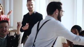 Ο ευτυχής νέος καυκάσιος αρσενικός προϊστάμενος περπατά κατά μήκος του σύγχρονου ελαφριού γραφείου που δίνει τα υψηλά fives στους φιλμ μικρού μήκους