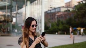 Ο ευτυχής νέος καυκάσιος θηλυκός ταξιδιώτης με το σακίδιο πλάτης στα γυαλιά ηλίου εξερευνά το ηλιόλουστο πάρκο του Μπρούκλιν, παί απόθεμα βίντεο