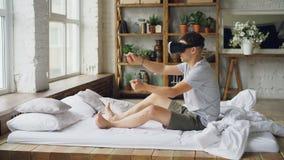Ο ευτυχής νεαρός άνδρας στα γυαλιά εικονικής πραγματικότητας κάθεται σε ετοιμότητα το κρεβάτι και κινούμενα σαν οδηγεί τη γυρίζον φιλμ μικρού μήκους