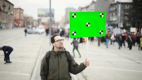 Ο ευτυχής νεαρός άνδρας στην επίδειξη πόλεων κρατά την αφίσα με την πράσινη οθόνη στο χέρι του απόθεμα βίντεο