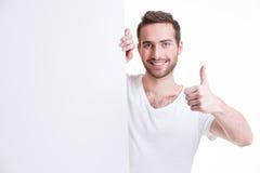 Ο ευτυχής νεαρός άνδρας κοιτάζει έξω από το κενό έμβλημα Στοκ Φωτογραφίες