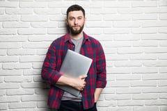 Ο ευτυχής νεαρός άνδρας παρουσιάζει lap-top στα χέρια ενάντια στο τουβλότοιχο Στοκ φωτογραφίες με δικαίωμα ελεύθερης χρήσης