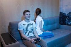 Ο ευτυχής νεαρός άνδρας που παίζει ένα τηλεοπτικό παιχνίδι με το του που προσβάλλεται Στοκ Εικόνα
