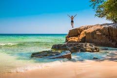 Ο ευτυχής νεαρός άνδρας που πηδά από τον απότομο βράχο στον ωκεανό στοκ εικόνα