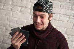 Ο ευτυχής νεαρός άνδρας σε μια ΚΑΠ και το πουλόβερ που κρατά τρία smartphones στο χέρι του και εξετάζουν τους Στοκ Εικόνα