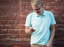 Ο ευτυχής νεαρός άνδρας στα γυαλιά που κλίνουν ενάντια στο τουβλότοιχο και κοιτάζει βιαστικά το Διαδίκτυο στο έξυπνο κινητό τηλέφ Στοκ Εικόνα