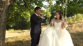 Ο ευτυχής νεόνυμφος στο κοστούμι και η νύφη στο άσπρο φόρεμα πίνουν τη σαμπάνια από τα όμορφα ποτήρια κρασιού και το γύρο στην τα απόθεμα βίντεο