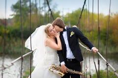 Ο ευτυχής νεόνυμφος φιλά τη νύφη στη γέφυρα στη ημέρα γάμου τους στοκ φωτογραφία
