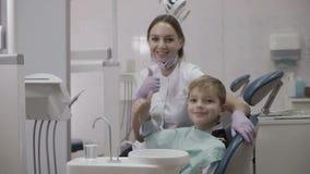 Ο ευτυχής οδοντίατρος και λίγος ασθενής παρουσιάζουν αντίχειρα φιλμ μικρού μήκους