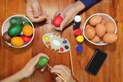 Ο ευτυχής οικογενειακός χρόνος κατά τη διάρκεια προετοιμάζει τα αυγά για την ημέρα Πάσχας Στοκ Εικόνες