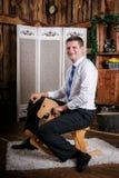 Ο ευτυχής παιδαριώδης νεαρός άνδρας οδηγά στο ξύλινο άλογο παιχνιδιών στοκ φωτογραφία με δικαίωμα ελεύθερης χρήσης
