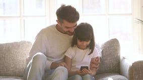 Ο ευτυχής πατέρας και λίγη κόρη που χρησιμοποιούν το smartphone κάθονται στον καναπέ απόθεμα βίντεο