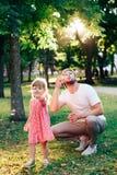 Ο ευτυχής πατέρας με μια μικρή κόρη στο φυσώντας σαπούνι ηλιοβασιλέματος βράζει σε ένα θερινό πάρκο υπαίθρια Στοκ Εικόνες