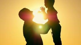 Ο ευτυχής πατέρας ρίχνει με αργό ρυθμό το παιδί επάνω και τον πιάνει Σκιαγραφία μιας ευτυχούς οικογένειας απόθεμα βίντεο