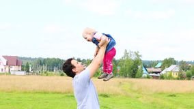 Ο ευτυχής πατέρας ρίχνει τη μικρή κόρη του στο πράσινο λιβάδι φιλμ μικρού μήκους