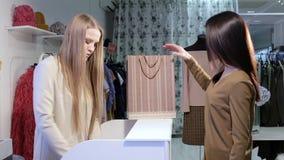 Ο ευτυχής πελάτης πληρώνει με την πιστωτική κάρτα για τα αγορασμένα ενδύματα στεμένος στο γραφείο ταμιών ` s φιλμ μικρού μήκους