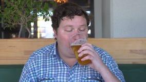 Ο ευτυχής πιωμένος νεαρός άνδρας με ένα γυαλί του οινοπνεύματος κατανάλωσης μπύρας και παίρνει μεθυσμένος απόθεμα βίντεο
