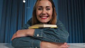 Ο ευτυχής σπουδαστής κοριτσιών σε ένα πουκάμισο τζιν αγκαλιάζει ευτυχώς έναν μεγάλο σωρό βιβλίων Κινηματογράφηση σε πρώτο πλάνο απόθεμα βίντεο