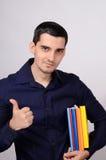 Ο ευτυχής σπουδαστής που κρατά έναν σωρό των βιβλίων κάτω από την υπογραφή βραχιόνων του φυλλομετρεί επάνω. Στοκ φωτογραφία με δικαίωμα ελεύθερης χρήσης