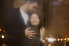 Ο ευτυχής τύπος αγάπης αγκαλιάζει τη φίλη του που στέκεται πίσω από ένα υγρό παράθυρο με τα φω'τα στοκ εικόνες