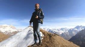 Ο ευτυχής φωτογράφος ταξιδιωτικών γενειοφόρος ατόμων στα γυαλιά ηλίου με μια κάμερα και ένα σακίδιο πλάτης πηγαίνει ανηφορικά σε  απόθεμα βίντεο