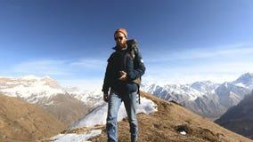 Ο ευτυχής φωτογράφος ταξιδιωτικών γενειοφόρος ατόμων στα γυαλιά ηλίου με μια κάμερα και ένα σακίδιο πλάτης πηγαίνει ανηφορικά σε  φιλμ μικρού μήκους