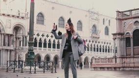 Ο ευτυχής χαμογελώντας θηλυκός τουρίστας με τα περιστέρια που κάθεται στο βραχίονα και το κεφάλι της παίρνει selfie στο τετράγωνο απόθεμα βίντεο