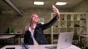Ο ευτυχής χαμογελώντας καυκάσιος ξανθός εργαζόμενος γραφείων κάθεται στο atble κοντινό λειτουργώντας εξοπλισμό και παίρνει selfie απόθεμα βίντεο