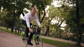 Ο ευτυχής, χαμογελώντας νεαρός άνδρας στο άσπρο πουκάμισο έχει έναν γύρο ποδηλάτων με την οδήγηση της πορείας στο πράσινο πάρκο π απόθεμα βίντεο