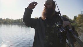 Ο ευτυχής χαμογελώντας ψαράς με τη μακριά γενειάδα περπατά στην όχθη ποταμού με την αλιεία των ράβδων κίνηση αργή απόθεμα βίντεο