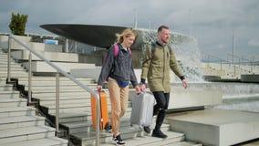 Ο ευτυχείς νεαρός άνδρας και η γυναίκα με τις βαλίτσες χαμηλώνουν πέρα από το σκαλοπάτι στην ηλιόλουστη οδό απόθεμα βίντεο