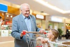 Ο ευτυχείς παππούς και το παιδί ψωνίζουν από κοινού Στοκ Φωτογραφίες