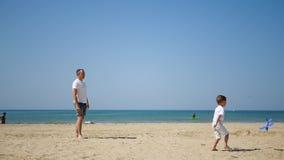 Ο ευτυχείς πατέρας και ο γιος στην αμμώδη παραλία θάλασσας μεταξύ τους προωθούν ένα αεροπλάνο παιχνιδιών φιλμ μικρού μήκους