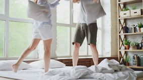 Ο ευτυχείς σύζυγος και η σύζυγος ζευγών έχουν την πάλη μαξιλαριών στο διπλό κρεβάτι, έχουν τη διασκέδαση που χαμογελά και που γελ φιλμ μικρού μήκους
