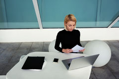 Ο ευφυής θηλυκός γραμματέας προετοιμάζει τις μηνιαίες εκθέσεις για τον προϊστάμενό της καθμένος στο εσωτερικό γραφείων Στοκ Εικόνες