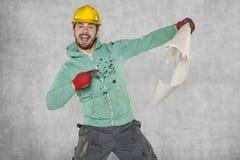 Ο ευχάριστα έκπληκτος εργαζόμενος δείχνει ένα σχέδιο κατασκευής Στοκ εικόνα με δικαίωμα ελεύθερης χρήσης