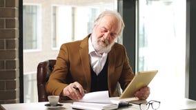 Ο ευχάριστος ηληκιωμένος ατόμων γράφει τις ιδέες του στο σημειωματάριο στο εσωτερικό φιλμ μικρού μήκους