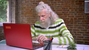 Ο ευχάριστος καυκάσιος ηληκιωμένος με την παχιά άσπρη δακτυλογράφηση γενειάδων στον υπολογιστή του συγκεντρώθηκε, περιλαμβάνείτε  φιλμ μικρού μήκους