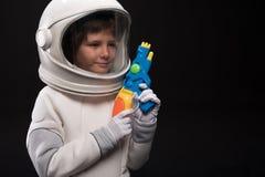Ο ευχάριστος κοσμοναύτης παιδιών παίζει με το πυροβόλο όπλο παιχνιδιών Στοκ Εικόνα