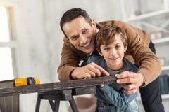 Ο ευχαριστημένος πατέρας που βοηθά το γιο του μετρά τον πίνακα στοκ φωτογραφία
