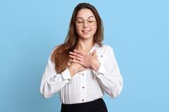 Ο ευχαριστημένος χαμογελώντας υπάλληλος λαμβάνει τον έπαινο από το κολλέγιό της, που κολακεύεται βαθειά, διαγώνια χέρια στο στήθο στοκ φωτογραφίες
