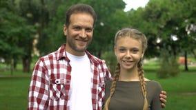 Ο εύθυμοι πατέρας και το έφηβη κόρη που χαμογελούν στη κάμερα, παρουσίαση φυλλομετρούν επάνω απόθεμα βίντεο