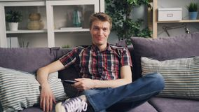 Ο εύθυμος άνδρας σπουδαστής προσέχει την αστεία κωμική σειρά στη TV και τη χαλάρωση γέλιου στον καναπέ και το κράτημα του τηλεχει απόθεμα βίντεο