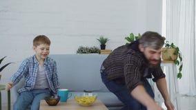 Ο εύθυμος αγαπώντας πατέρας παίζει με το μικρό γιο του που ρίχνει και ποδόσφαιρο λακτίσματος και κατανάλωση των πρόχειρων φαγητών φιλμ μικρού μήκους