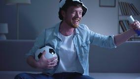Ο εύθυμος αρσενικός ανεμιστήρας με το ποδόσφαιρο αποδίδει το παιχνίδι προσοχής στη TV στο σπίτι, νίκη φιλμ μικρού μήκους